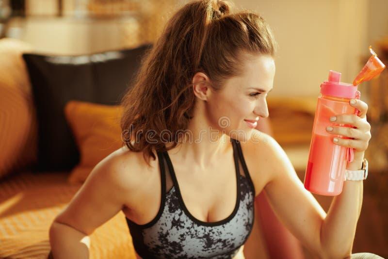 Mujer sonriente de los deportes con la coctelera con suplementos de la aptitud fotografía de archivo