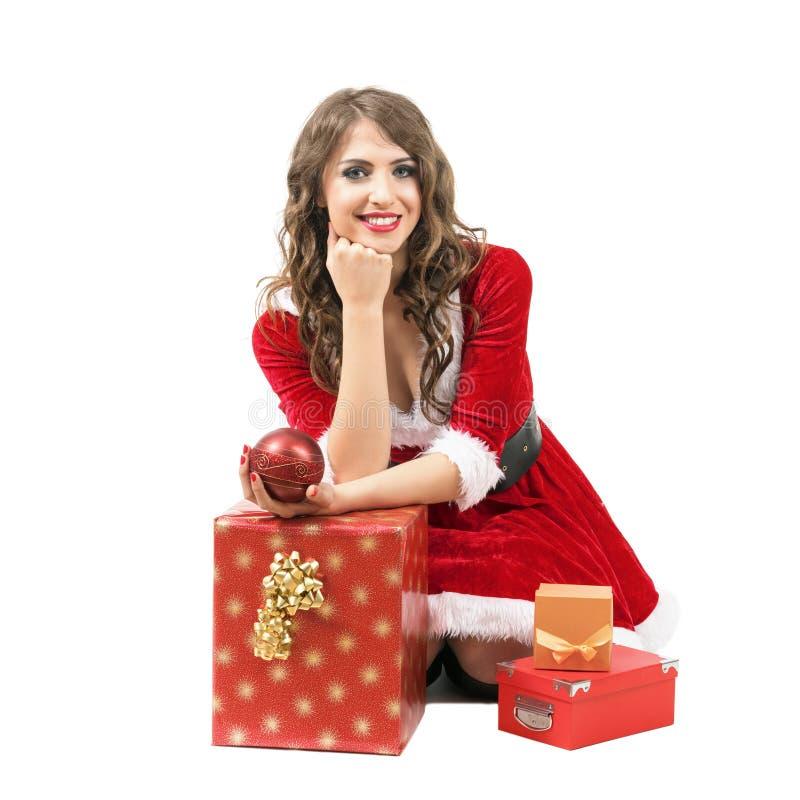 Mujer sonriente de Papá Noel que se sienta con la cabeza que descansa a mano alrededor de las cajas de regalo foto de archivo