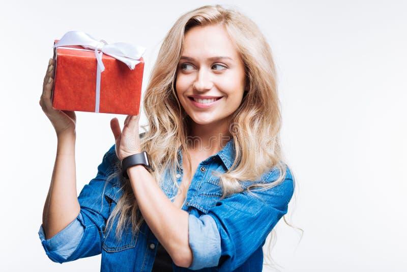 Mujer sonriente de pelo rubio que sostiene la caja de regalo imagenes de archivo