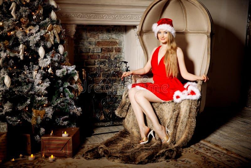 Mujer sonriente de santa de la belleza joven cerca del árbol de navidad Fashio foto de archivo