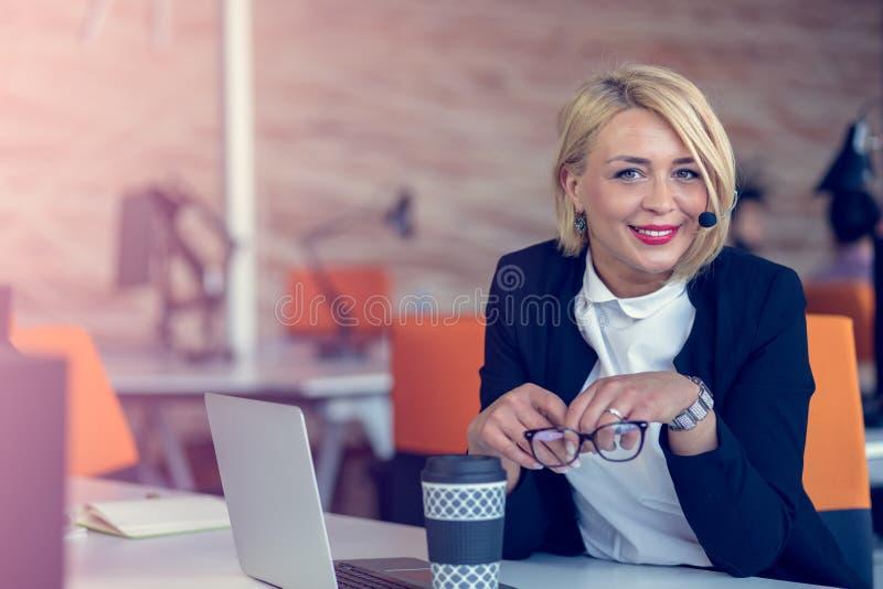 Mujer sonriente del agente con las auriculares Retrato del trabajador del centro de atención telefónica en la oficina fotos de archivo libres de regalías
