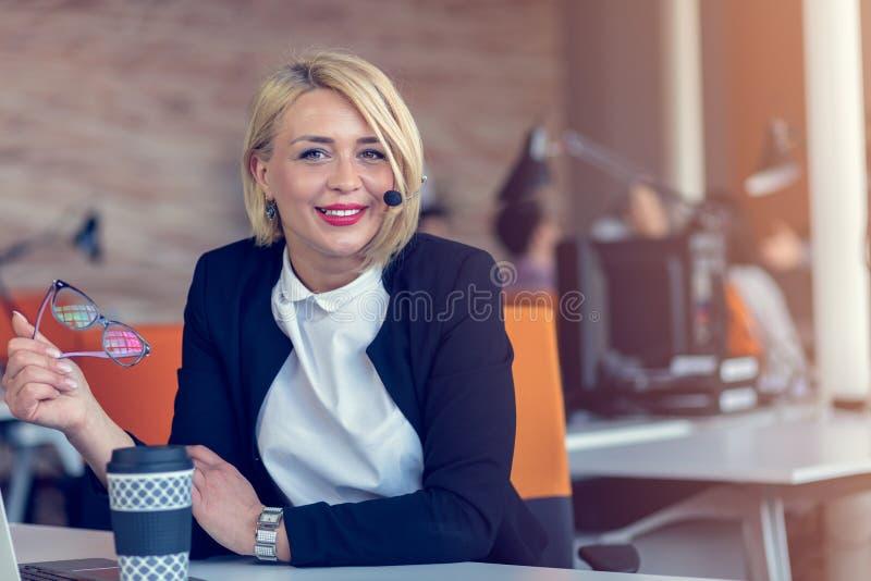 Mujer sonriente del agente con las auriculares Retrato del trabajador del centro de atención telefónica en la oficina imágenes de archivo libres de regalías