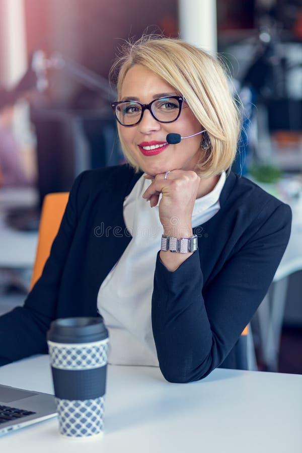 Mujer sonriente del agente con las auriculares Retrato del trabajador del centro de atención telefónica en la oficina fotos de archivo
