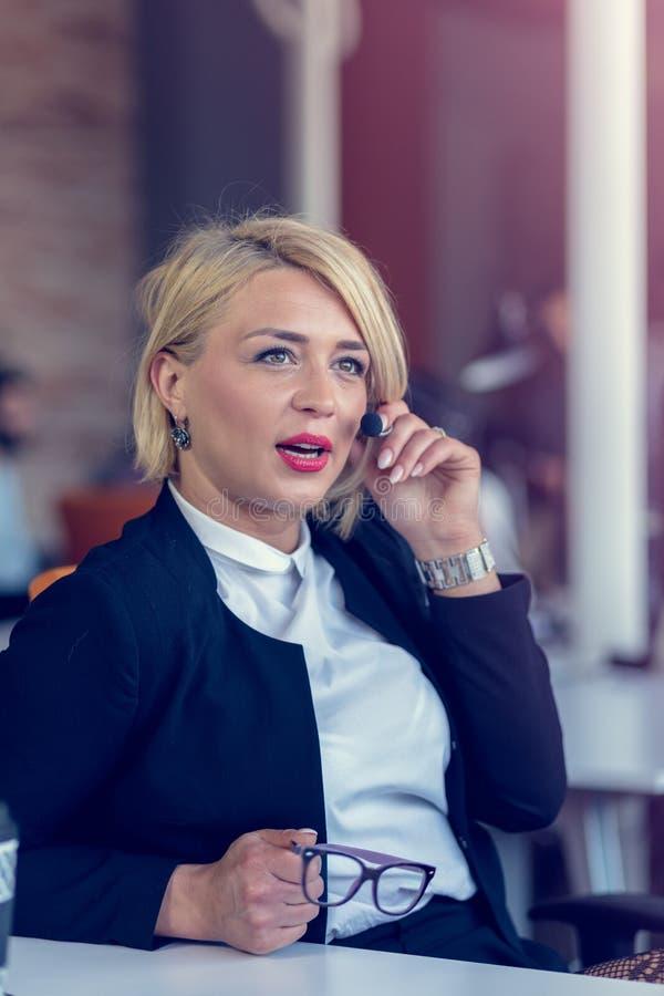 Mujer sonriente del agente con las auriculares Retrato del trabajador del centro de atención telefónica en la oficina imagen de archivo