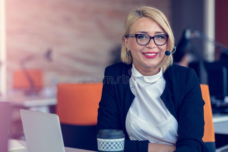 Mujer sonriente del agente con las auriculares Retrato del trabajador del centro de atención telefónica en la oficina foto de archivo