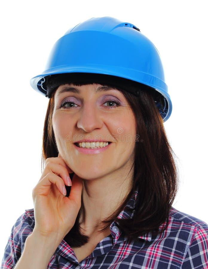 Mujer sonriente del constructor que lleva el casco azul protector fotografía de archivo