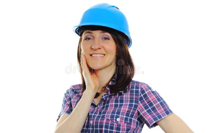 Mujer sonriente del constructor que lleva el casco azul protector foto de archivo libre de regalías