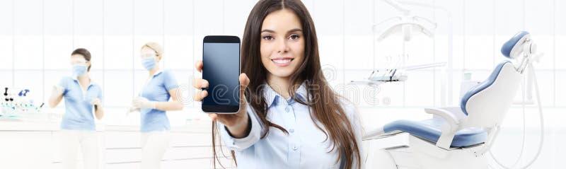 Mujer sonriente del cuidado dental que muestra el teléfono elegante en clínica del dentista fotografía de archivo