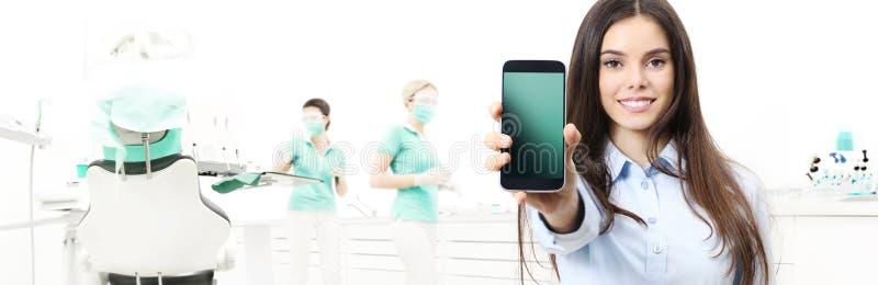 Mujer sonriente del cuidado dental que muestra el teléfono elegante en clínica del dentista imagenes de archivo