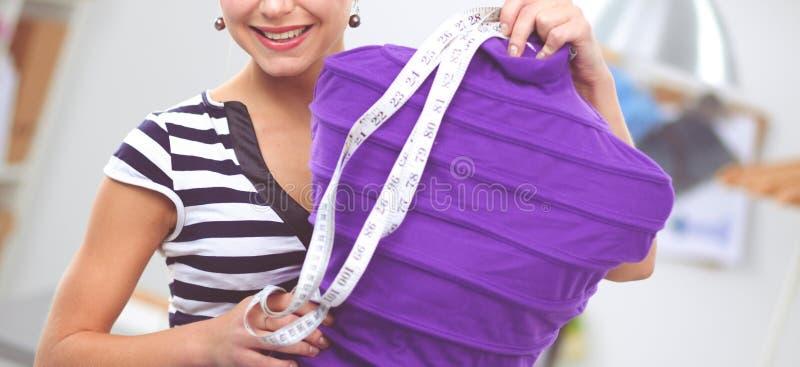 Mujer sonriente del dise?ador de moda que coloca el maniqu? cercano en oficina imagen de archivo libre de regalías
