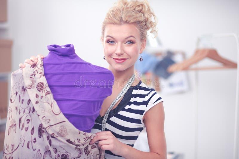 Mujer sonriente del dise?ador de moda que coloca el maniqu? cercano en oficina fotos de archivo
