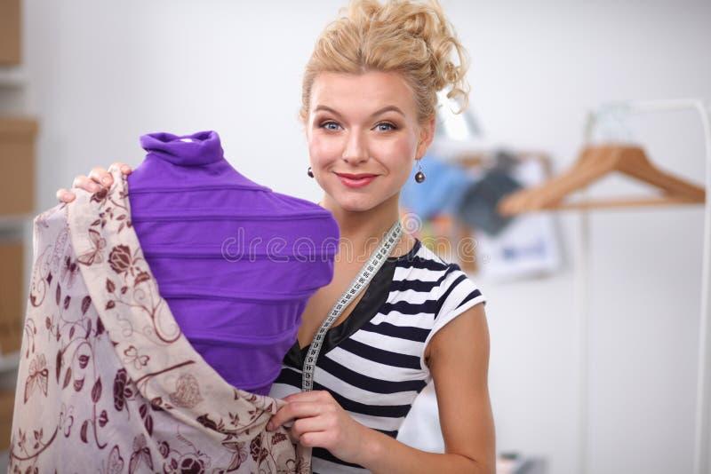 Mujer sonriente del dise?ador de moda que coloca el maniqu? cercano en oficina foto de archivo libre de regalías