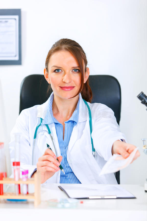 Mujer sonriente del doctor que da la prescripción médica foto de archivo libre de regalías