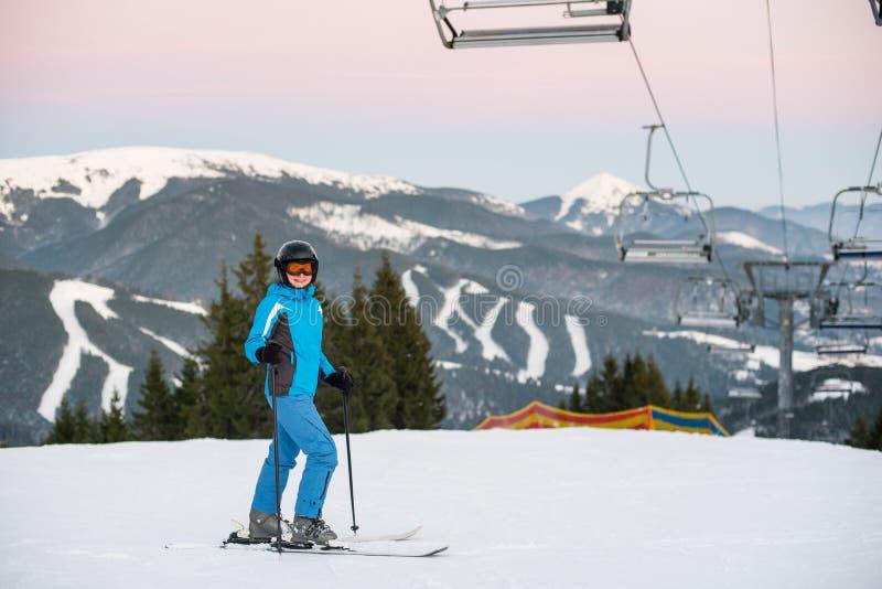Mujer sonriente del esquí que se coloca en montaña de la nieve debajo del funicular imagen de archivo libre de regalías