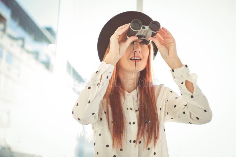 Mujer sonriente del inconformista que usa los prismáticos imagen de archivo