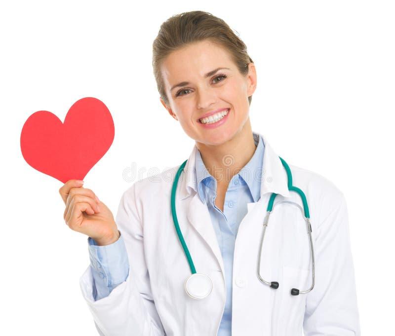Mujer sonriente del médico que lleva a cabo el corazón de papel imagenes de archivo