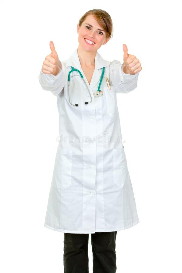 Mujer sonriente del médico que muestra los pulgares para arriba foto de archivo