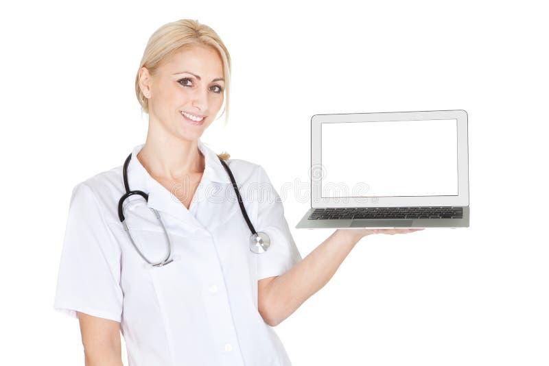 Mujer sonriente del médico que presenta la computadora portátil fotografía de archivo