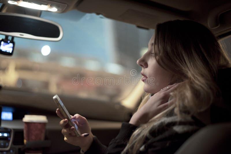 Mujer sonriente del pasajero que usa el teléfono móvil foto de archivo