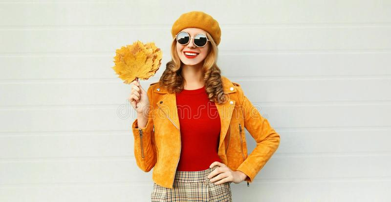Mujer sonriente del retrato del otoño que sostiene las hojas de arce amarillas que llevan la boina francesa que presenta en la ca imagenes de archivo