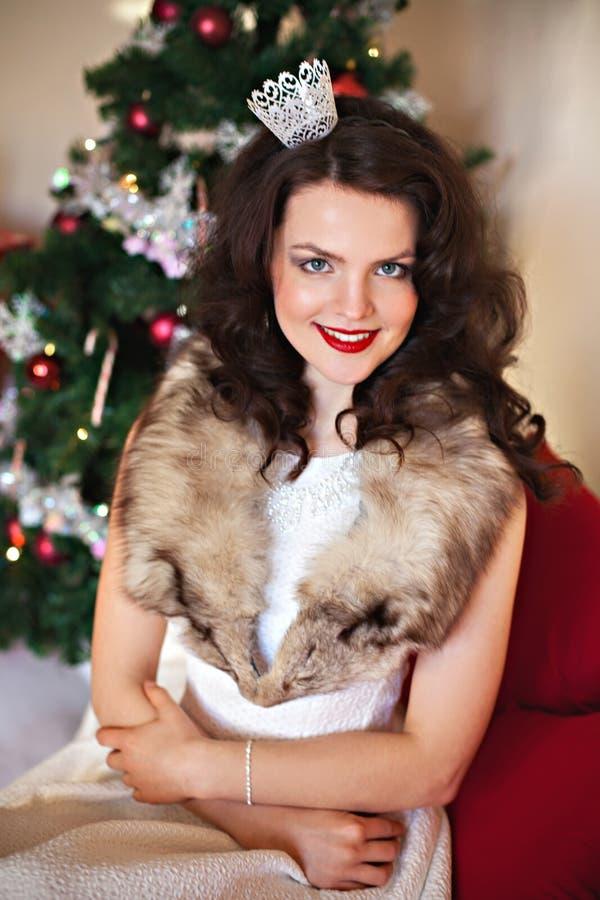 Mujer sonriente delante del árbol de navidad imagenes de archivo