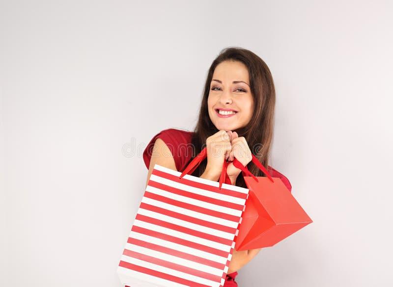 Mujer sonriente dentuda feliz joven con los bolsos de compras Días de fiesta de la Feliz Año Nuevo imagenes de archivo