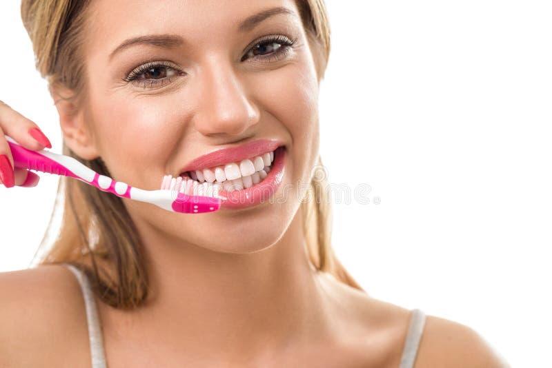 Mujer sonriente durante los dientes de cepillado imagen de archivo