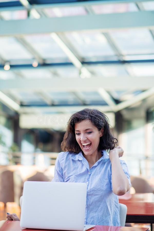 Mujer sonriente emocionada que celebra triunfo en l?nea, usando el ordenador port?til en caf?, mirando la pantalla, gritando con  foto de archivo