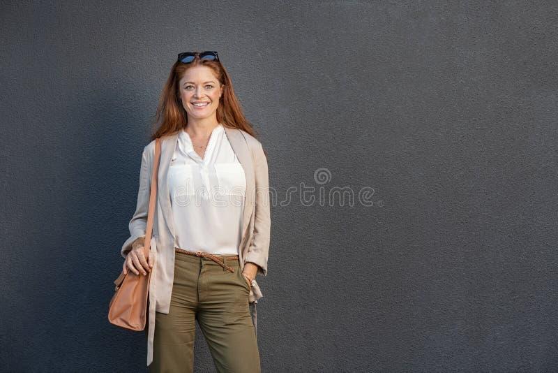 Mujer sonriente en casual aislada en la pared gris imagen de archivo libre de regalías