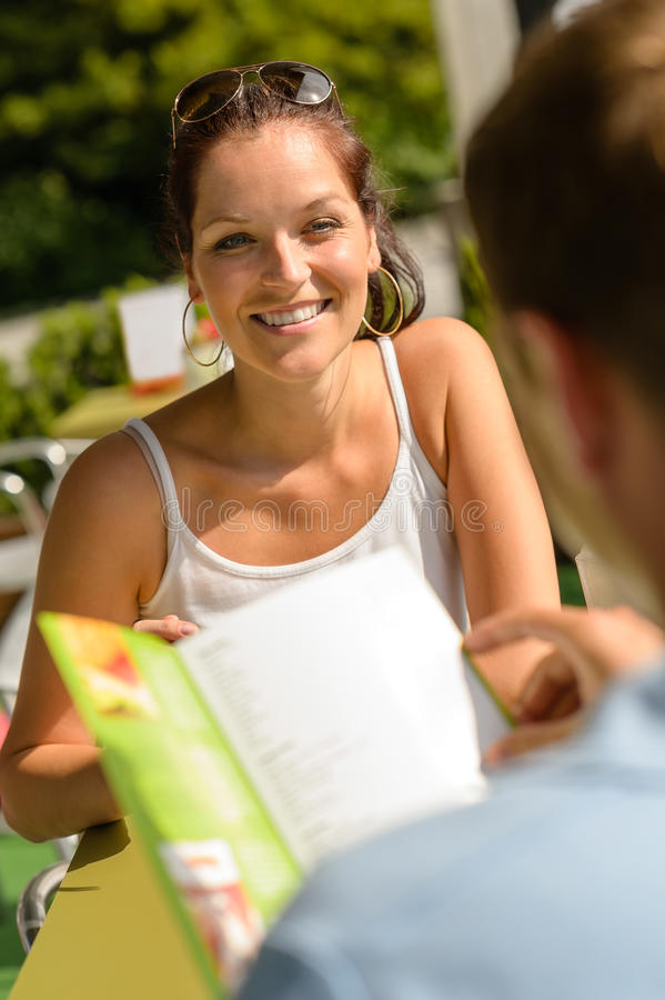 Mujer sonriente en el almuerzo de los pares de la terraza del restaurante foto de archivo