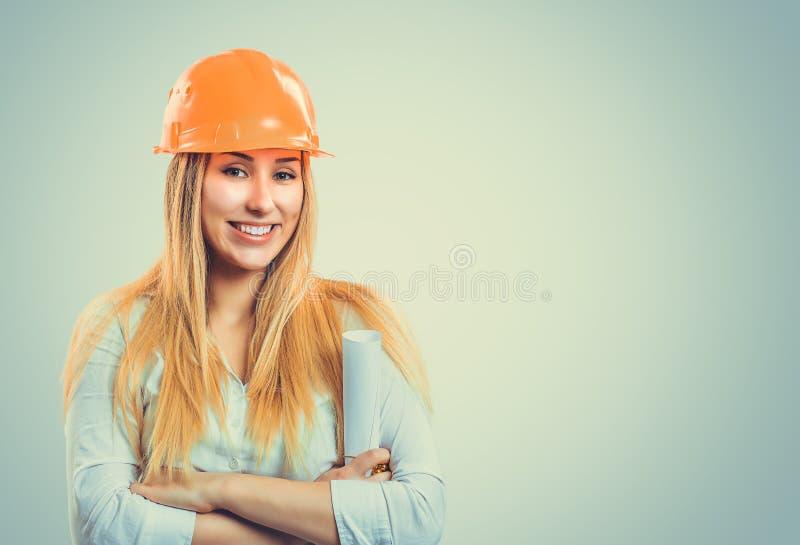 Mujer sonriente en el casco de protección que lleva a cabo planes foto de archivo