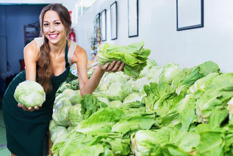 Mujer sonriente en el delantal que vende lechuga fresca foto de archivo