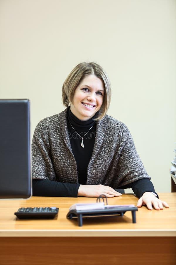 Mujer sonriente en el desc con el monitor de computadora imagenes de archivo