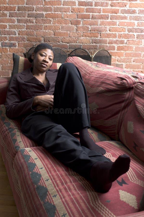Mujer sonriente en el sofá fotos de archivo libres de regalías