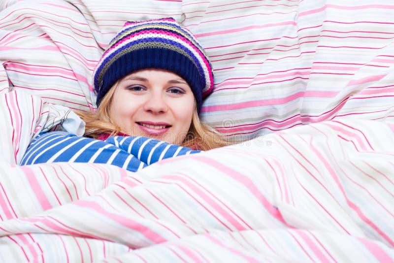 Mujer sonriente en el sombrero del invierno envuelto en duvet fotografía de archivo libre de regalías