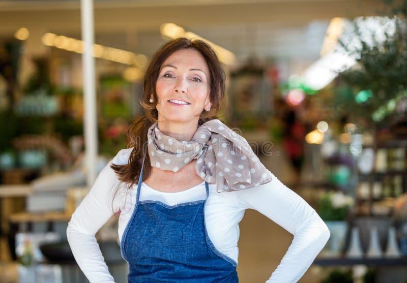 Mujer sonriente en floristería foto de archivo libre de regalías