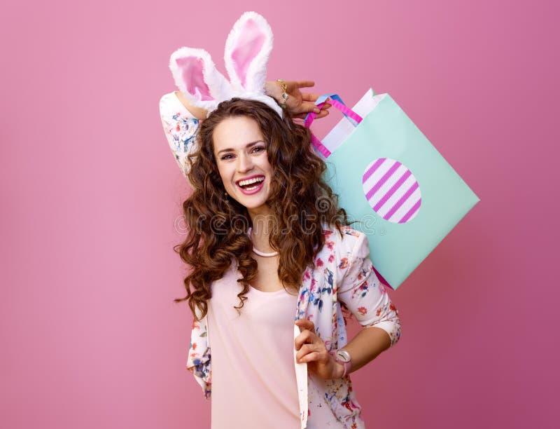 Mujer sonriente en fondo rosado con el panier de Pascua imagen de archivo libre de regalías