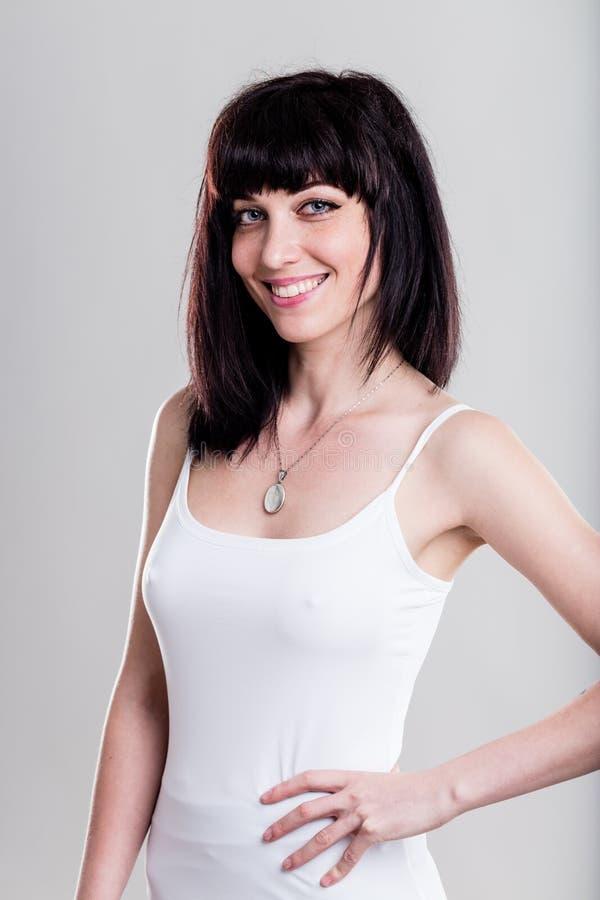 Mujer sonriente en la camisa blanca apretada (versión visible de las entrerroscas) fotos de archivo