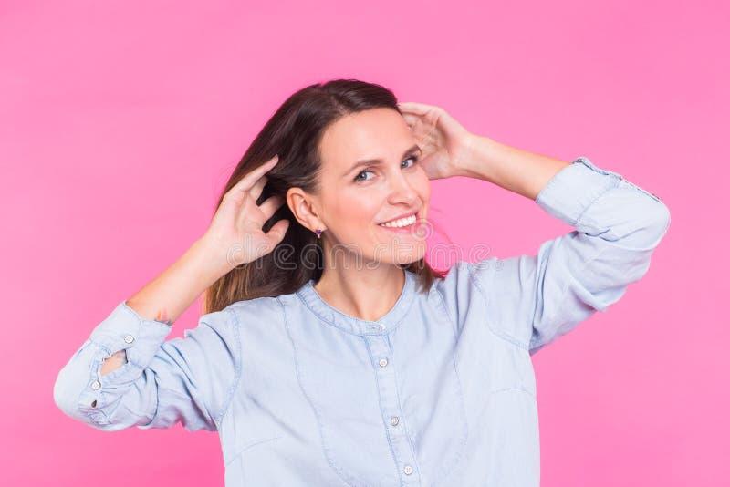 Mujer sonriente en la camisa que presenta en estudio en fondo rosado imagenes de archivo