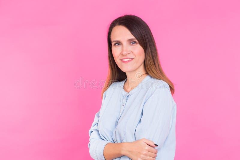 Mujer sonriente en la camisa que presenta en estudio en fondo rosado fotografía de archivo libre de regalías