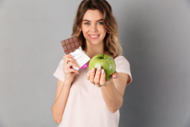 Mujer sonriente en la camiseta que celebra el chocolate y el donante de la manzana fresca fotos de archivo libres de regalías