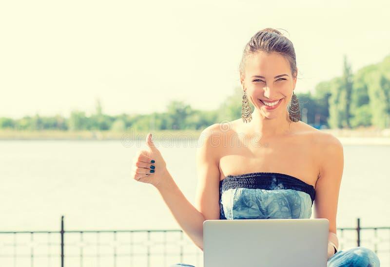 Mujer sonriente en la playa que se sienta en hierba con el ordenador imagen de archivo libre de regalías