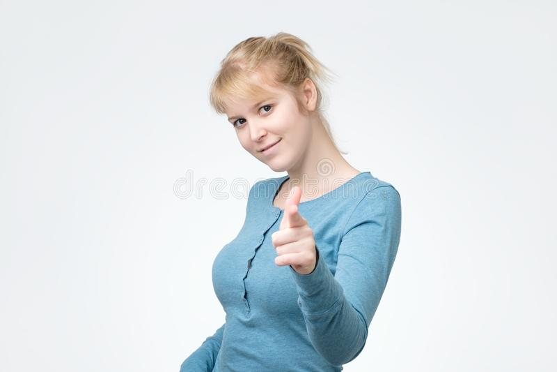 Mujer sonriente en longsleeve azul que señala en usted imagen de archivo libre de regalías