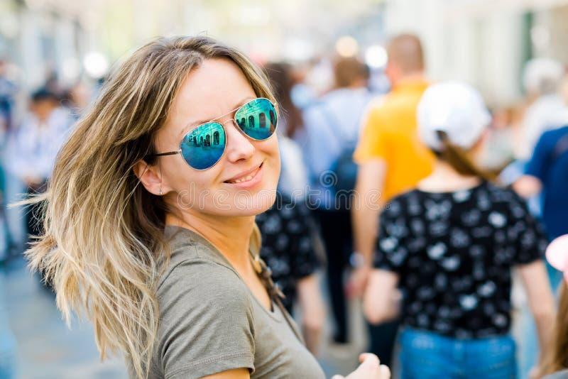 Mujer sonriente en los vidrios de sol que miran detrás en una ciudad foto de archivo