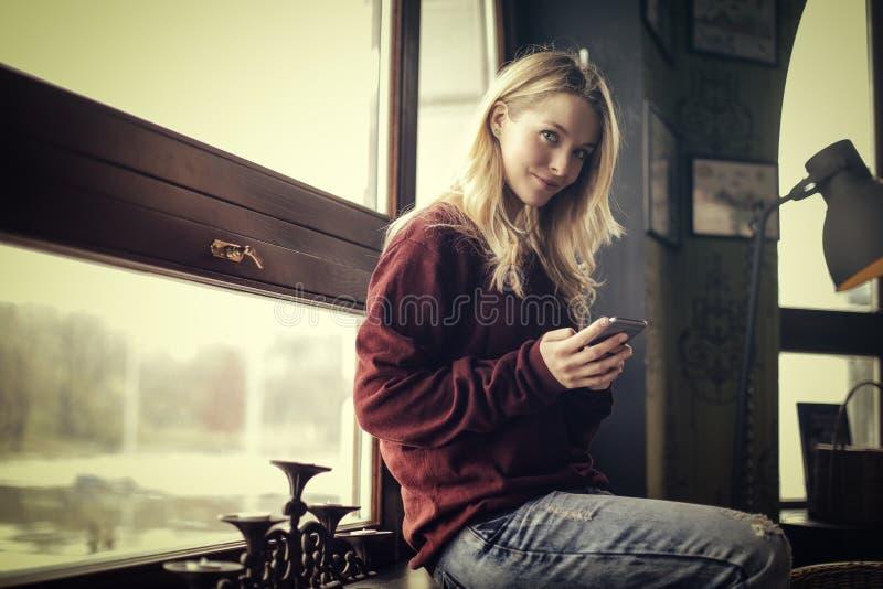 Mujer sonriente en su teléfono imágenes de archivo libres de regalías