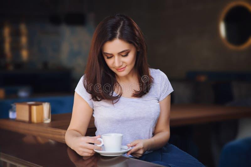 Mujer sonriente en un buen humor con la taza de café que se sienta en café fotografía de archivo