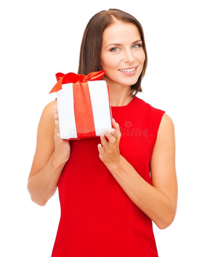Mujer sonriente en vestido rojo con la caja de regalo foto de archivo