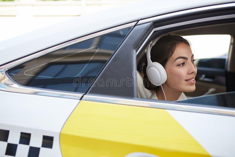 Mujer sonriente en vista lateral del taxi imágenes de archivo libres de regalías