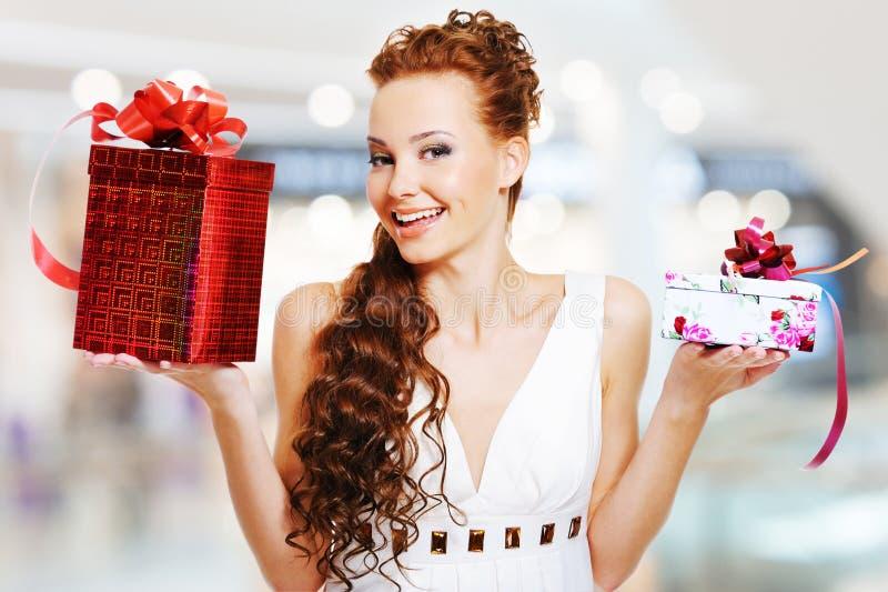 Mujer sonriente feliz con el presente de cumpleaños en manos fotos de archivo libres de regalías