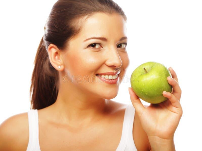 Mujer sonriente feliz con la manzana verde imagenes de archivo